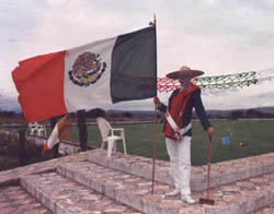 Dr. Bett Yates Adams, San Miguel resident player, USCA member-at-large, and first female publisher (retired) in the New York Times chain, hoists the flag in full regalia to dramatize the opening of Mexico's newest court.